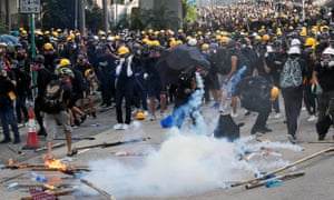 Protesters move away from teargas thrown by police.