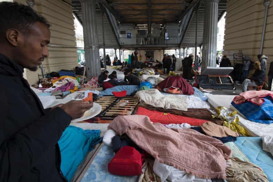 A migrant eats at a makeshift camp in Paris near the Stalingrad subway station