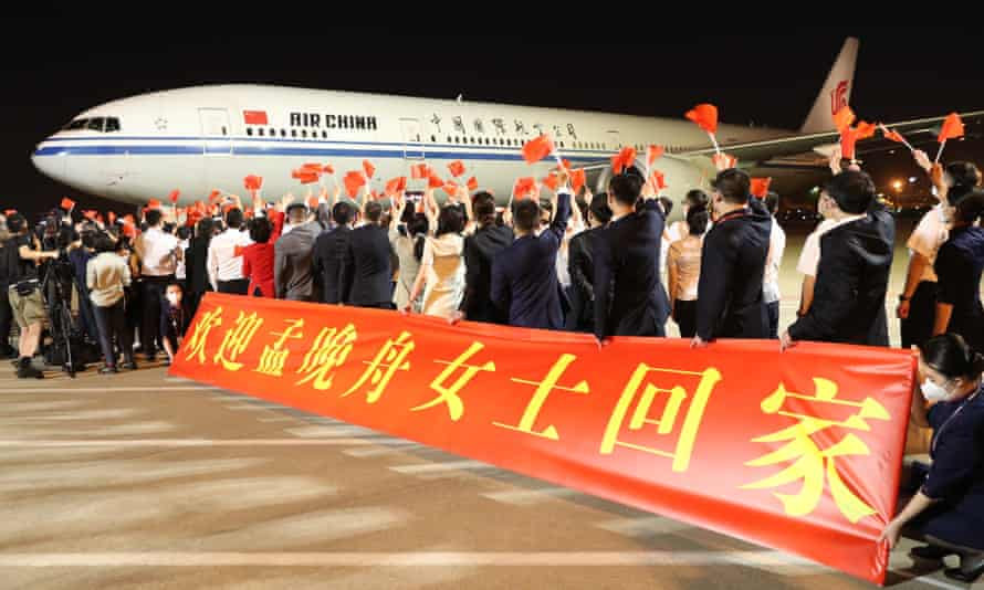 A crowd holds up a banner reading 'Welcome home, Ms Meng Wanzhou' at Shenzhen's Bao'an international airport on 25 September.