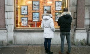 A couple look into an estate agency window