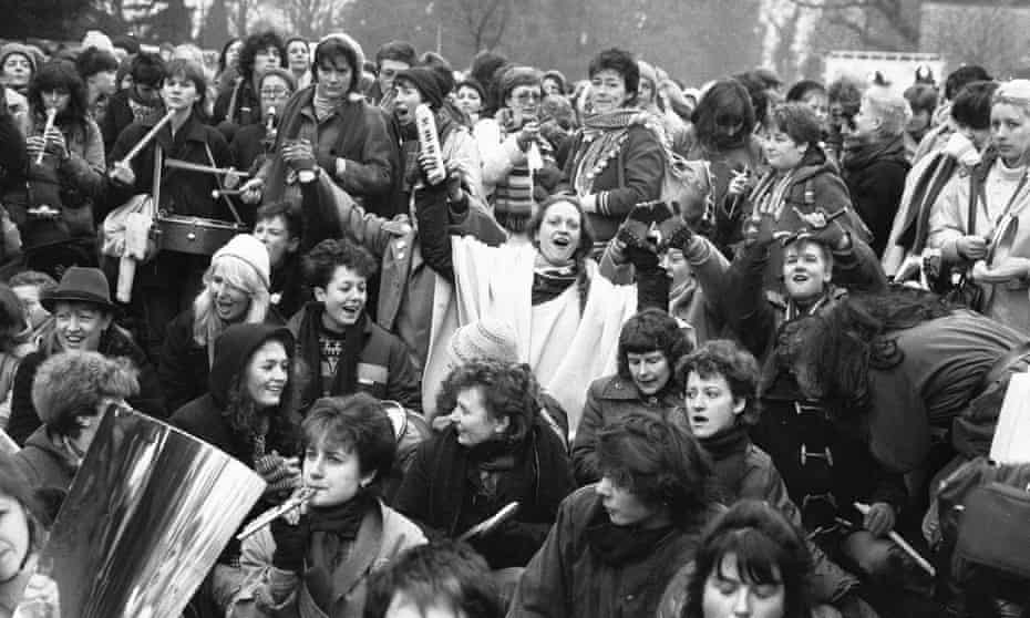 Women peace protesters sit down in the road to block one of the gates to RAF Greenham Common in December 1983.