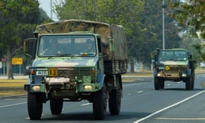 Military transport vehicles loaded with bottled water travel along a road in Bairnsdale, Victoria, on 4 January.