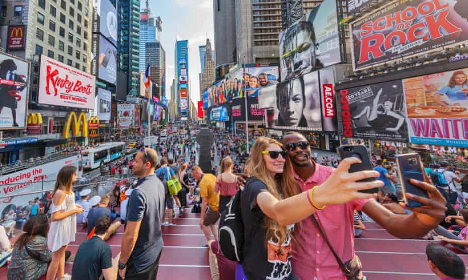 Tourists taking selfies in Times Square, New York.
