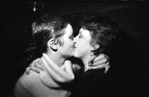 """Punk fans kissing at The Ranch, 1977 – Kevin Cummins """"The Ranch was a gay club owned by Mancunian drag star Foo Foo Lamarr. It became a popular haunt for punks in 1976, hosting gigs by Buzzcocks and The Fall. There was a degree of crossover between Manchester's queer and punk scenes at this time. This kiss doesn't look very sexual to me. I think these girls are just larking about."""""""