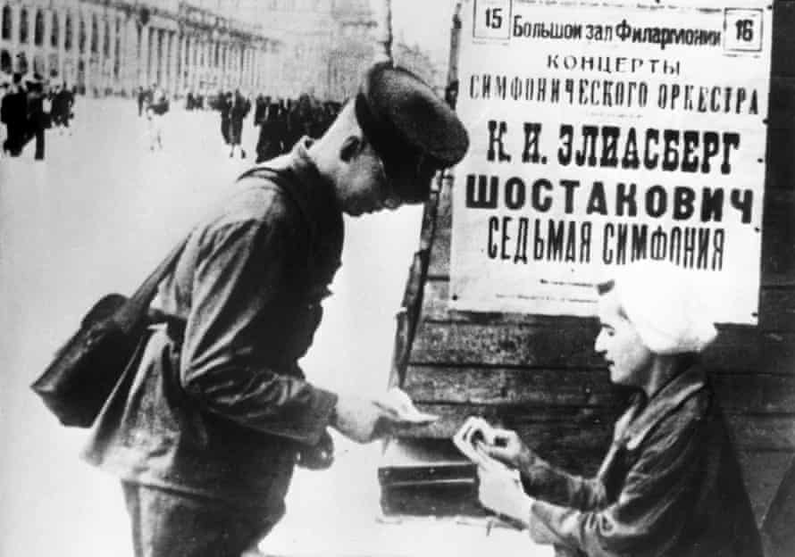 A soldier buys a ticket to a performance of Shostakovich's seventh symphony in front a billboard advertising the event, Leningrad, 1942.