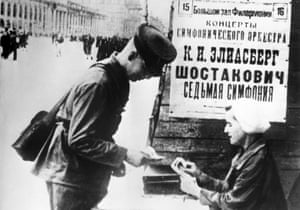 A Soviet soldier buys a ticket to the performance of Shostakovich's 7th Symphony, in Leningrad, 1942, announced by a billboard.