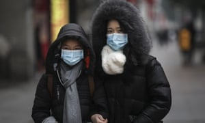 A family wears masks while walking in the street in Wuhan, Hubei province, China. Taken on 22 January.