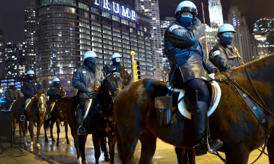 Police on horseback watch a small group of demonstrators protest near Trump Tower in Chicago on 7 January.