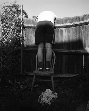 A man on a chair leaning over a fence