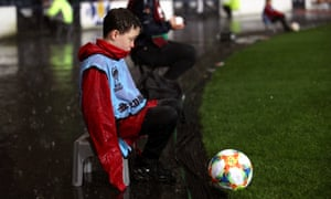 A ballboy sits in the rain during a Euro 2020 qualifying match at Hampden Park, Glasgow.