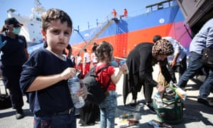 People receive food and water after disembarking from a vessel at the port of Heraklion on the island of Crete.