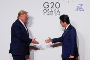 US President Donald Trump and Japan's Prime Minister Shinzo Abe shake hands at the G20