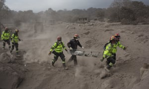 Rescue workers run for cover as Guatemala's Fuego volcano sends out more clouds of ash.