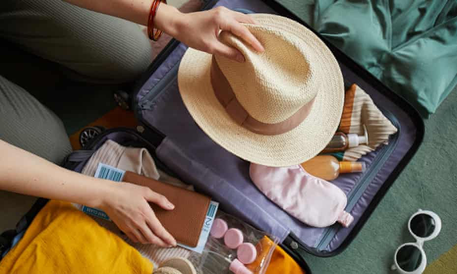 Close-up of woman packing her clothes in suitcase