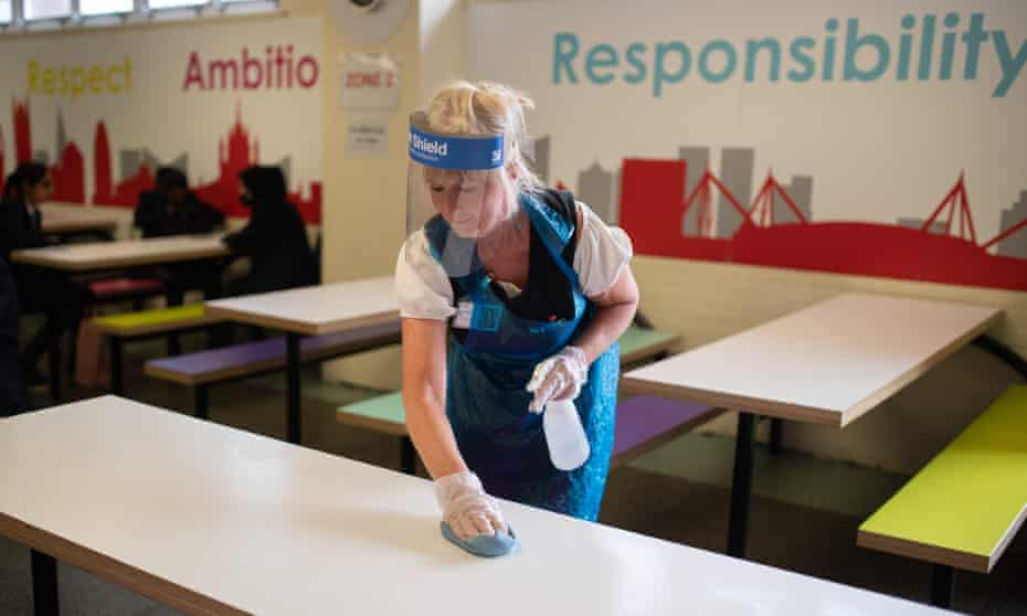 A cleaner wearing PPE sanitises furniture in the dining room of a school in Huddersfield, northern England.