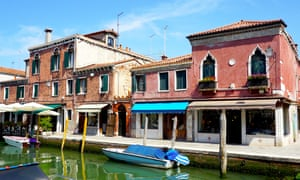 Boat on a canal outside a parade of shops in Murano, Veneto, Italy.