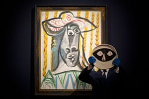 London, UK A Christie's specialist poses for photographs holding Pablo Picasso's glazed ceramic plate Tete au masque in front of the Picasso painting Tete. The painting features is estimated to fetch 4.8 to 6.5 million pounds and the ceramic plate is estimated to fetch 6,000 to 8,000 pounds