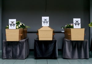 Coffins of Covid-19 victims are marked with a 'Biohazard' warning sign as they are placed next to each other at a funeral service in Belgium, 03 April 2020.