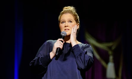 Comedian Amy Schumer with a mic in one hand, and the other held to her face