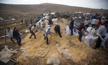 Palestinians collect grain after the Israeli army destroyed a storage structure in the West Bank.