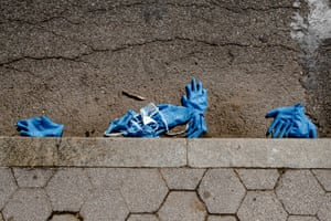 Gloves and surgical masks line the curb outside a Covid-19 testing facility at the Brooklyn Medical Center in Brooklyn, New York on 25 March 2020. Photo By Jordan Gale
