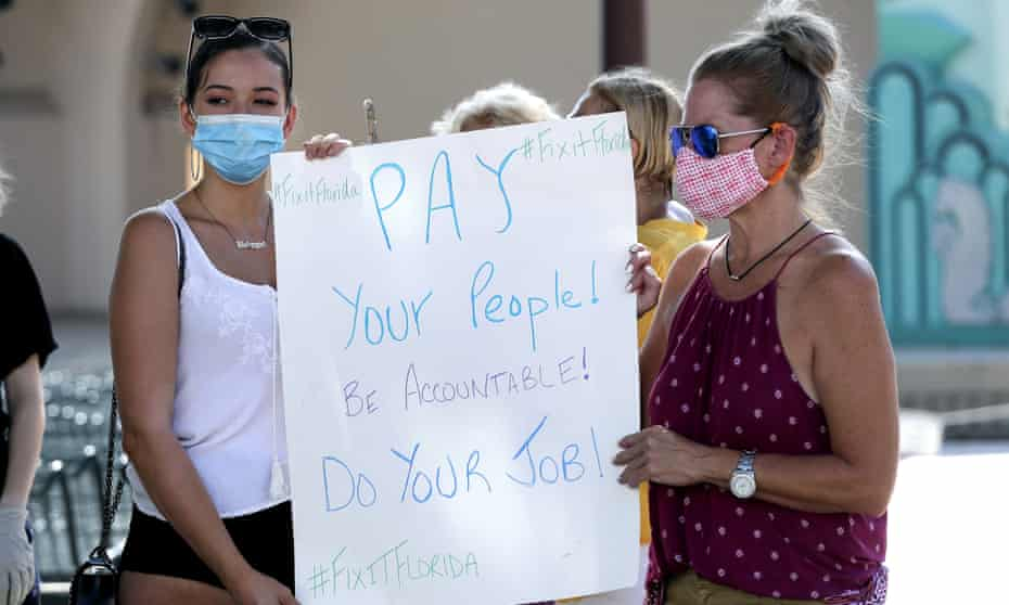 A small group of demonstrators gathers at Lake Eola Park to protest the Florida unemployment benefits system, Wednesday, June 10, 2020, in Orlando, Fla. Many Florida unemployed workers are still trying to apply for and receive unemployment benefits since the start of the coronavirus pandemic. (AP Photo/John Raoux)