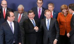 European Council President Donald Tusk (C-R) greets Turkish Prime Minister Ahmet Davutoglu