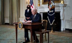 Joe Biden signs an executive order on the economy with Kamala Harris.