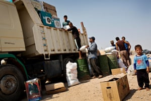 A boy stands next to a truck as his family load up their possession to return to Mosul