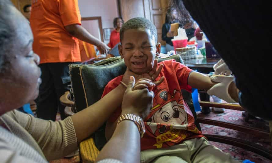 Grant Porter, five, reacts as his mother Ardis Porter tries to comfort him while having his blood drawn to be tested for lead in Flint, Michigan.