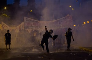 An anti-austerity protester throws a bottle at riot police in Athens