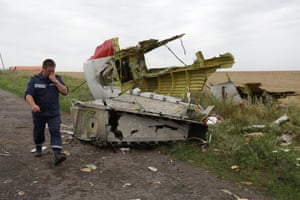 A Ukrainian rescue worker passing wreckage of the Boeing 777, Malaysia Arilines flight MH17 on 18 July 2014.