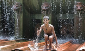 A boy plays in a fountain to cool off on a hot summer day in New Delhi.