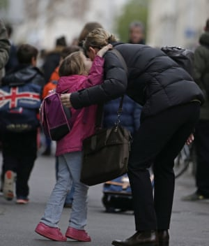 A child kisses a relative outside their school. Teachers have struggled to explain the killings to their pupils.