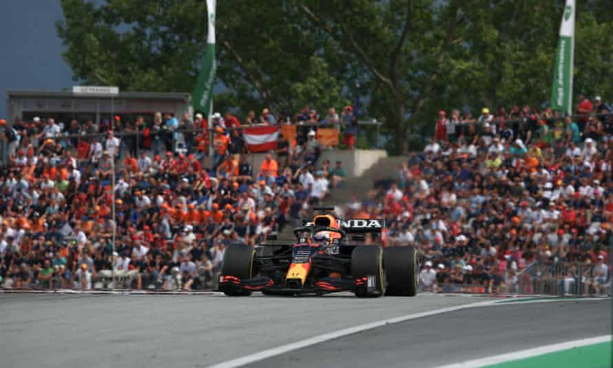 Max Verstappen drives past orange-clad supporters in the stands at the Red Bull Ring