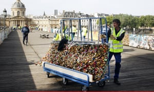 A council worker pushing a trolley of locks he has just removed from the Pont des Arts bridge