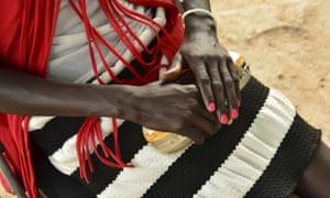 A woman clutches a gold handbag