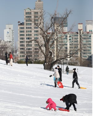 People enjoy sledging at Olympic Park in Seoul, South Korea, as heavy snowfall hit the nation