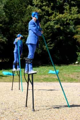 Harbingers … stilt walkers stalk the gardens.