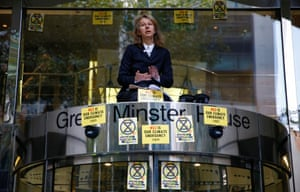 London, England The co-founder of Extinction Rebellion Gail Bradbrook sits atop the doorway in the Department for Transport during a protest