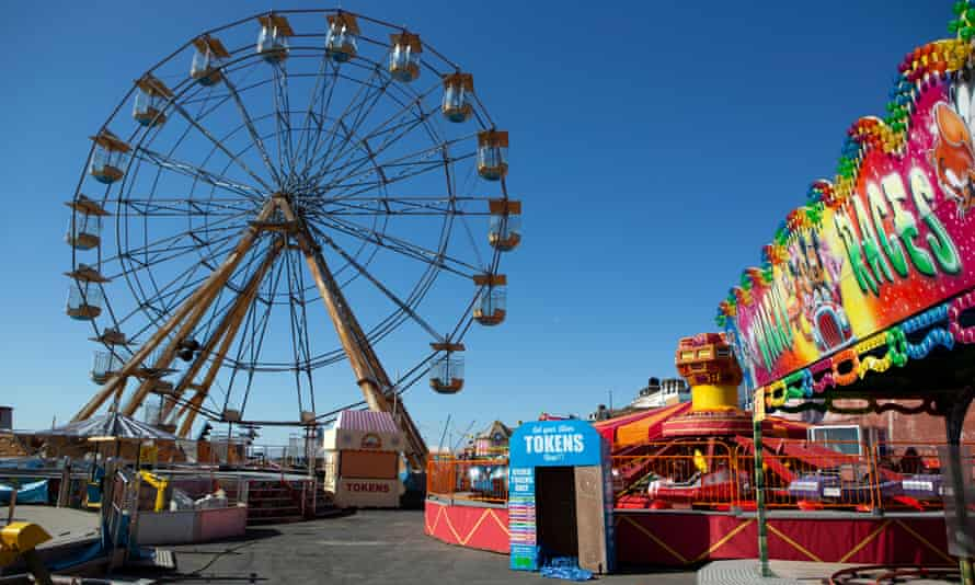 An empty ferris wheel and other rides at a funfair in Bridlington, North Yorkshire.