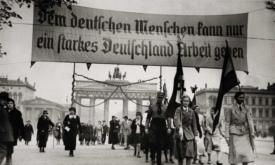 A column of people, led by two women carrying Nazi flags, and others  a huge banner saying 'Dem deutschen Menschen kann nur ein starkes Deutschland Arbeit geben'