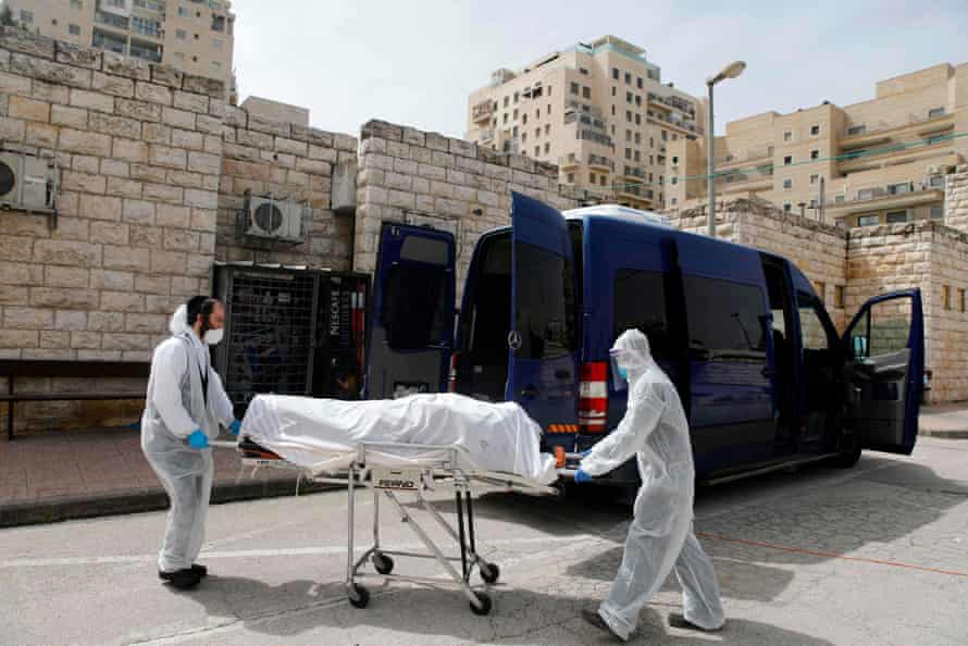 Ultra-Orthodox Jewish burial society workers with a coronavirus victim outside the Shamgar funeral house in Jerusalem.