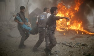 Emergency personnel carry a wounded man after air strikes by Syrian government forces on a marketplace in the rebel-held area of Douma on Sunday 16 August