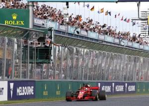 Ferrari driver Sebastian Vettel of Germany waves as he crosses the finish line to win the Australian Formula One Grand Prix in Melbourne.