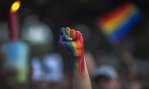 A person's raised fist painted in the colours of the LGBT rainbow flag