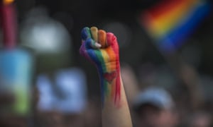 A defiant fist painted with the rainbow flag is raised