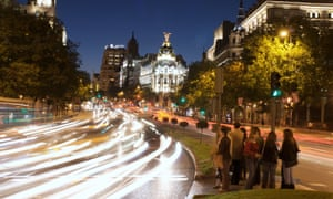 Cars pass through Madrid's Gran Via, with the city hall in the background.