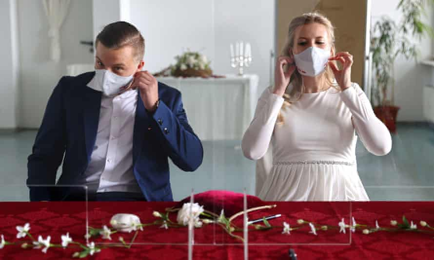 A couple remove their masks before their wedding.