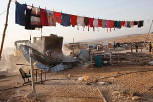 Clothes hang on a washing line next to a Palestinian home bulldozed by Israeli authorities in Umm al-Kheir